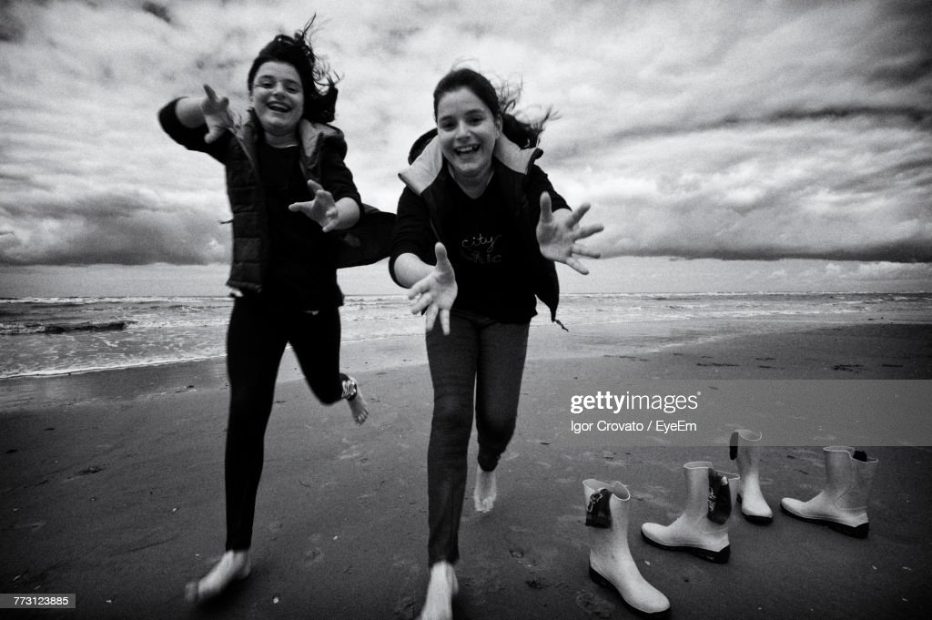 Playful Friends Running At Beach Against Sky : Photo