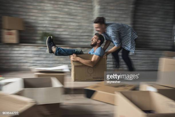 Playful gay couple having fun while playing with cardboard box in new apartment. Blurred motion.