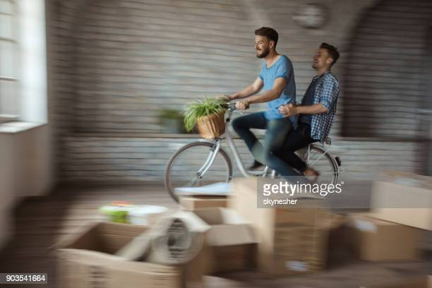 Playful gay men having fun on a bicycle at their new apartment. Blurred motion.