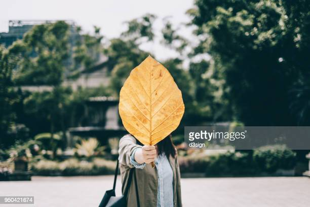 Playful girl covering face behind fallen yellow leaf in park