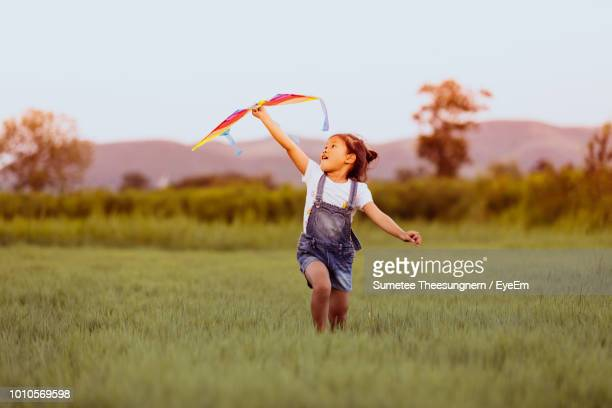 playful girl holding kite while running on grassy field at park - kite stock pictures, royalty-free photos & images