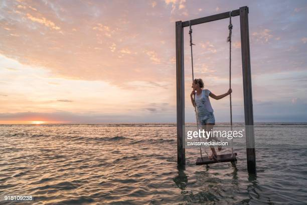 playful girl in paradise, sea swing at sunset - gili trawangan stock photos and pictures