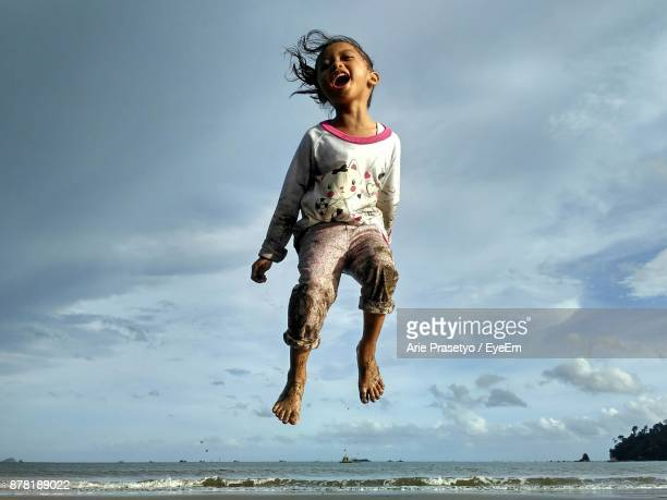 Playful Girl Jumping Over Sea Against Sky