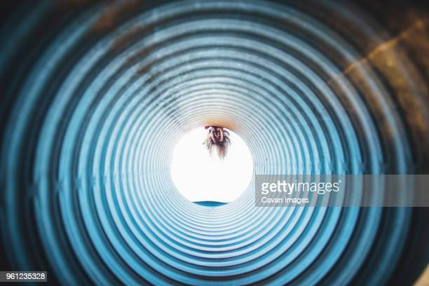 playful girl peeking through tube at playground - peeping holes ストックフォトと画像