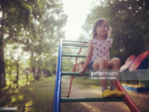 playful girl puckering while playing at playground - spielgerät stock-fotos und bilder