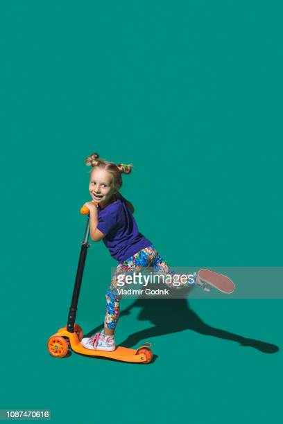 playful girl riding scoter on green background - scooter stock pictures, royalty-free photos & images