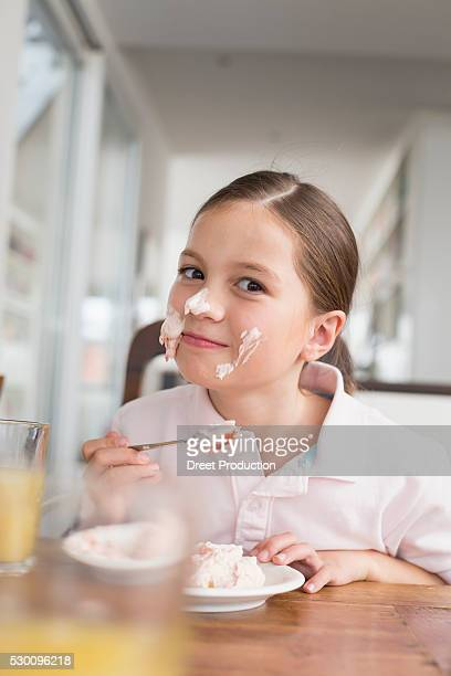 Playful girl smearing cake on her face