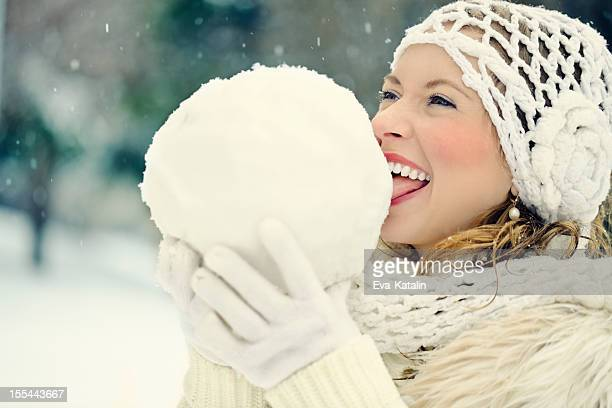 Playful girl tasting a big snowball