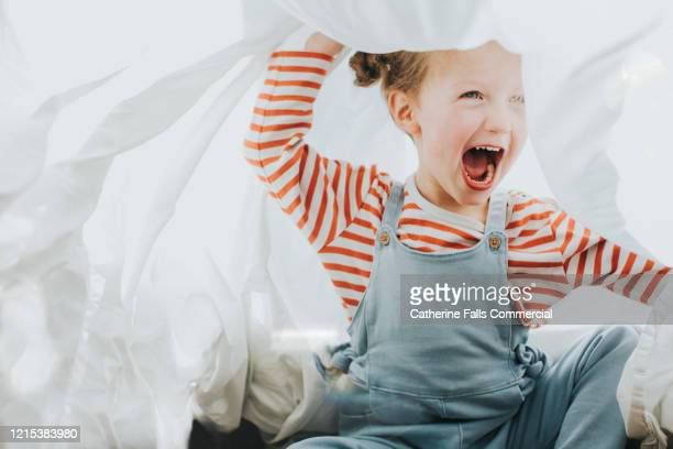 playful girl under a white sheet - waschen stock-fotos und bilder