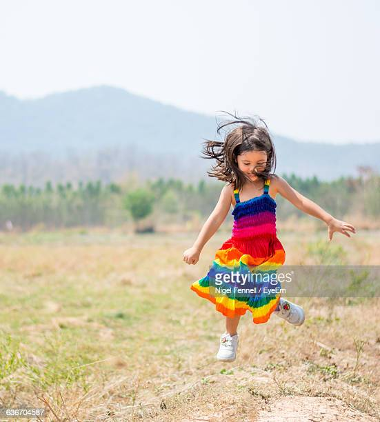 playful girl wearing multi colored dress jumping on field against sky - multi colored dress stock pictures, royalty-free photos & images