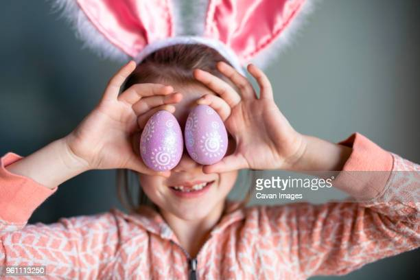 playful girl wearing rabbit ears headband while holding easter eggs at home - easter stock pictures, royalty-free photos & images