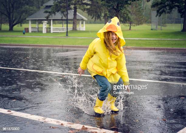 Playful girl wearing raincoat while jumping in puddle during rainfall