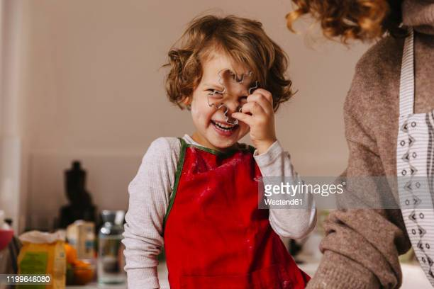 playful girl with her mother holding christmas cookie cutter in kitchen - 焼く ストックフォトと画像