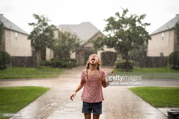 playful girl with mouth open standing on driveway during rainfall - nass stock-fotos und bilder