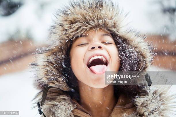 playful girl with mouth open tasting snow during snowfall - girls open mouth stock-fotos und bilder