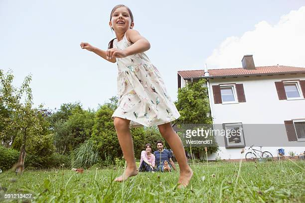 Playful girl with parents in garden