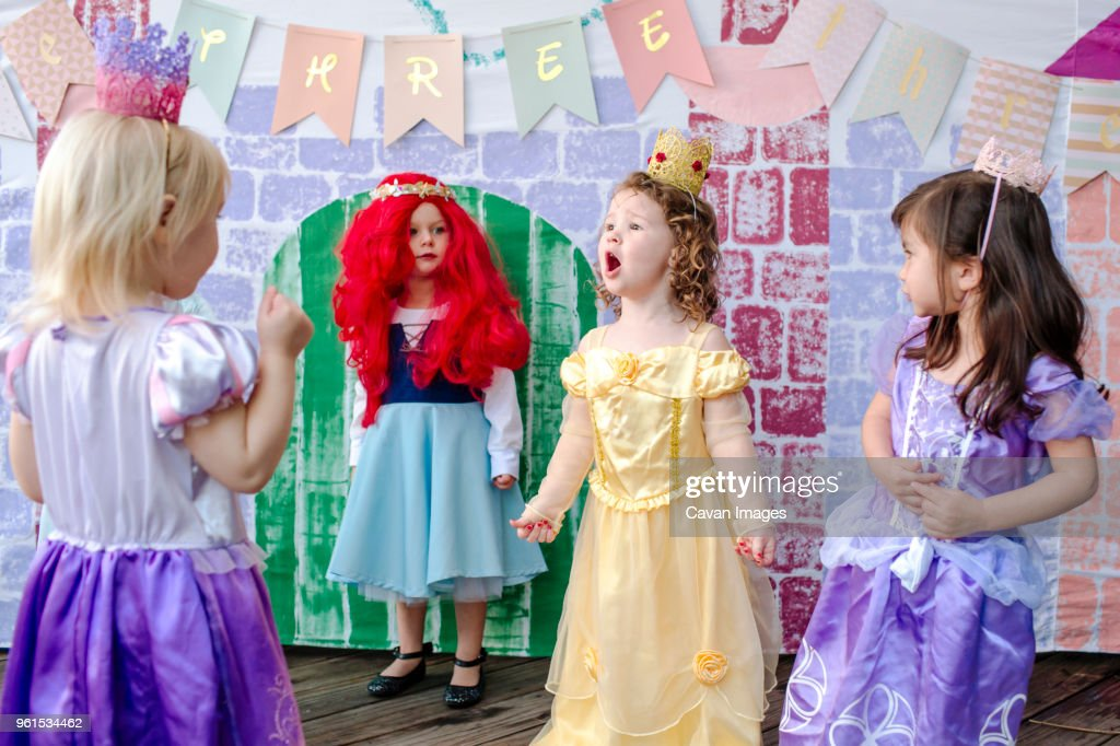 playful girls against castle painting during princess party stock