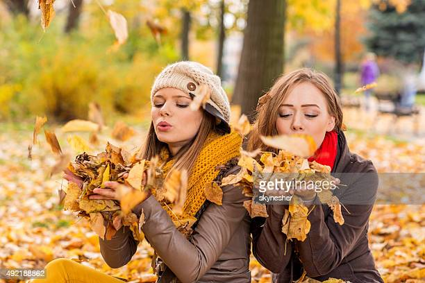 playful girls having fun in autumn park. - girl mound stock pictures, royalty-free photos & images