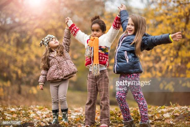 playful girls holding hands and having fun in the park. - in the park day 3 imagens e fotografias de stock