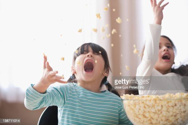 playful girls throwing popcorn - naughty america stock pictures, royalty-free photos & images