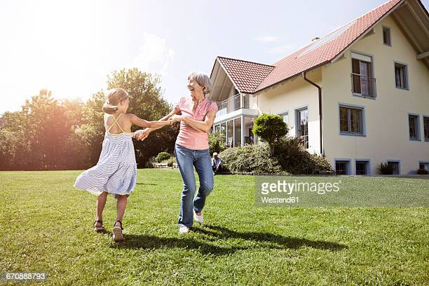 Playful grandmother with granddaughter in garden