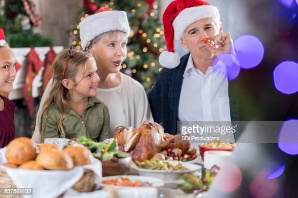Playful grandpa enjoys Christmas meal with family