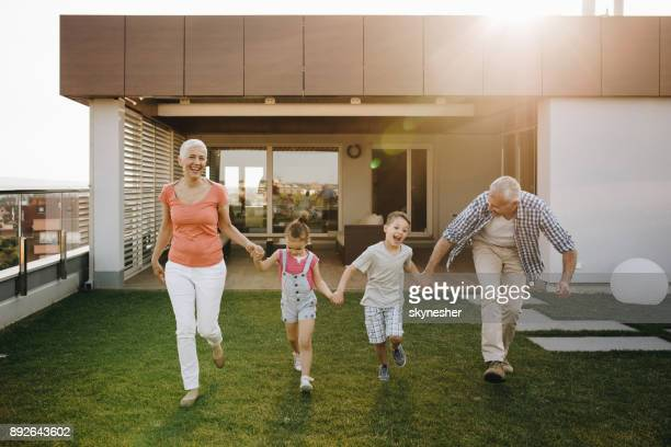 Playful grandparents and grandkids holding hands and running on a penthouse terrace.