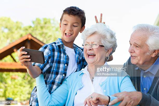 Playful grandparents and grandson take selfie