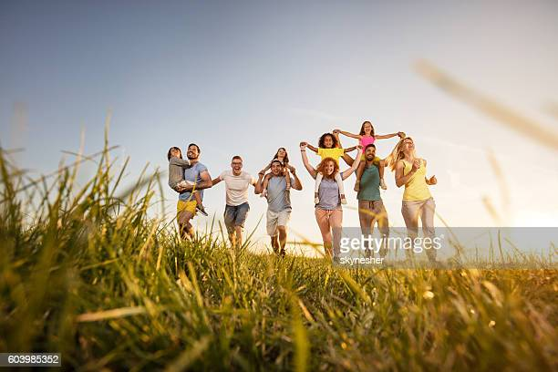 Playful group of people having fun and running in nature.
