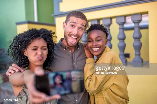 Playful happy friends taking a selfie outdoors
