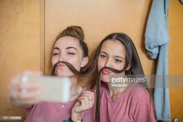 playful happy teenage girls taking a selfie - jeunes filles photos et images de collection