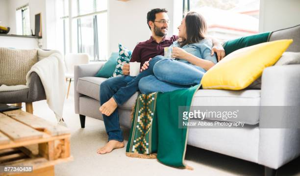 Playful hispanic couple relaxing at home.