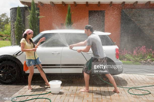Playful Hispanic couple washing car together
