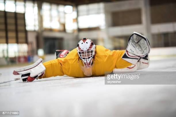 Ludique hockey sur glace glissant sur le ventre à la patinoire.