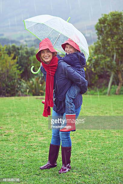 playful in the rain - mother son shower stock photos and pictures