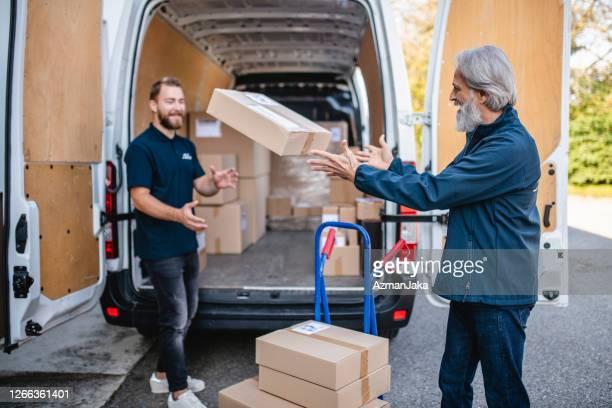 verspielte unabhängige fahrer tossing parzelle für das laden auf van - fangen stock-fotos und bilder