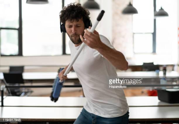 ほうきをシミュレートするオフィスで遊び心のある管理人は、ヘッドフォンで音楽を聴きながらギターです - 掃く ストックフォトと画像
