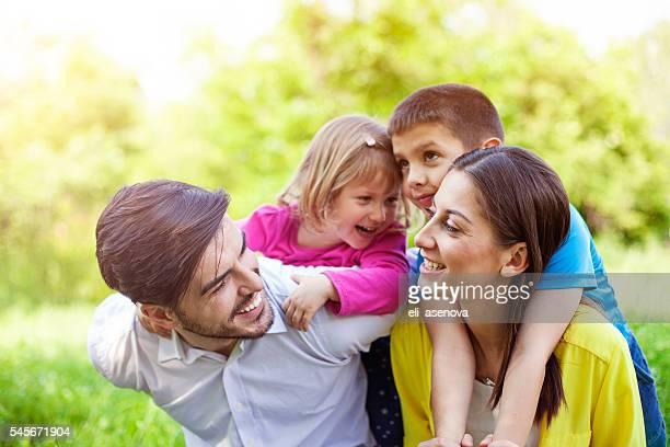 Playful Kids Enjoying Piggyback Ride On Parents Outdoors