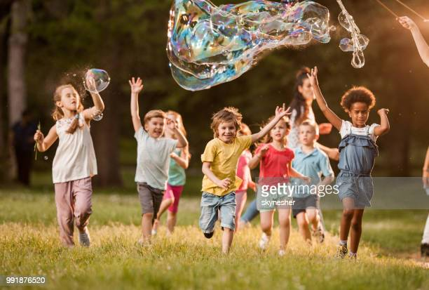 Playful kids having fun while running below rainbow bubbles in nature.