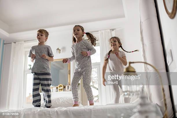 Playful kids jumping on a bed and having fun together.