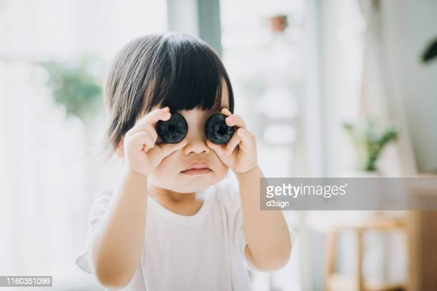 playful little asian toddler girl holding two huge blueberries over her eyes - hands covering eyes stock pictures, royalty-free photos & images