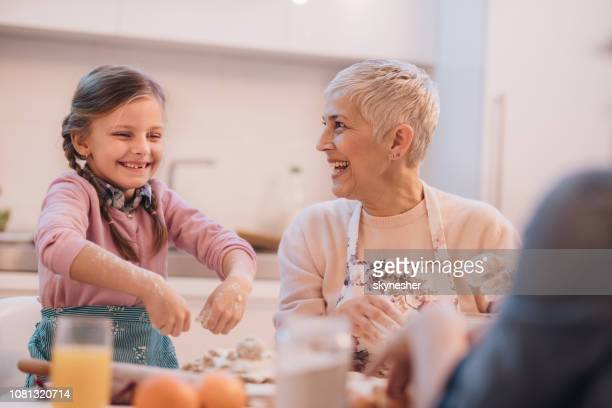 Playful little girl and her grandmother baking in the kitchen.