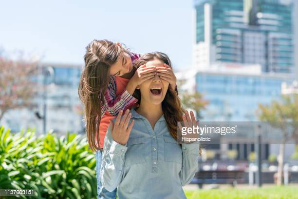 playful little girl covering her mother's eyes at the park - hispanolistic stock photos and pictures
