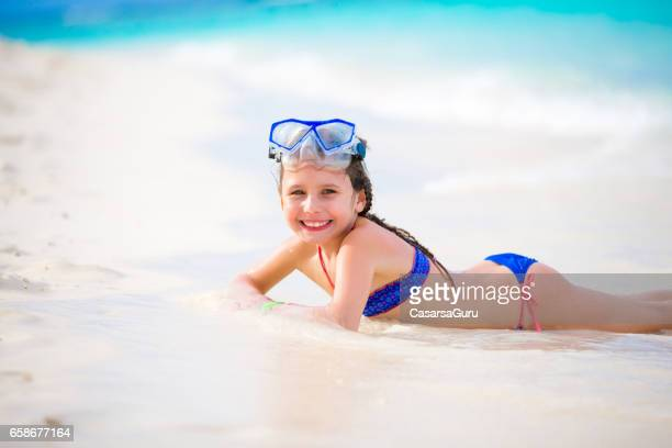 playful little girl enjoying on maldivies bech - little girl laying on the beach stock photos and pictures