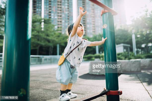 playful little toddler girl arms raised and trying to reach a pull up bar at the outdoor playground on a lovely sunny day - courage stock pictures, royalty-free photos & images