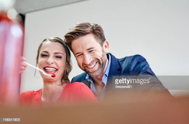 Playful man and woman sharing a raspberry