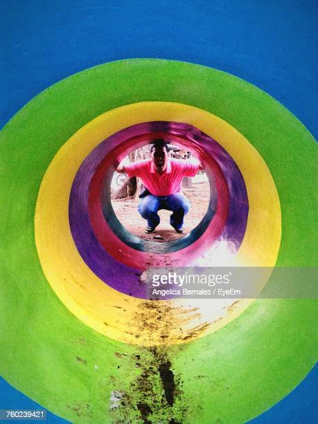Playful Man Crouching Towards Colorful Tunnel At Playground