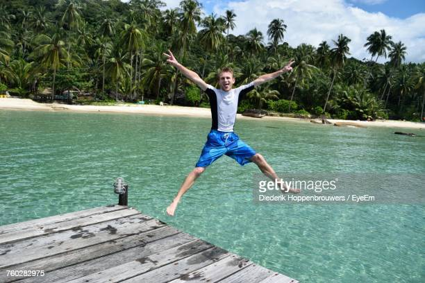 Playful Man Gesturing Peace Sign While Jumping In Sea