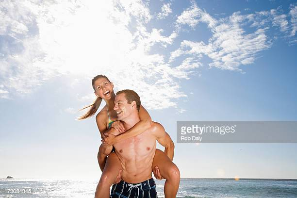 Playful man giving girlfriend piggyback ride on beach