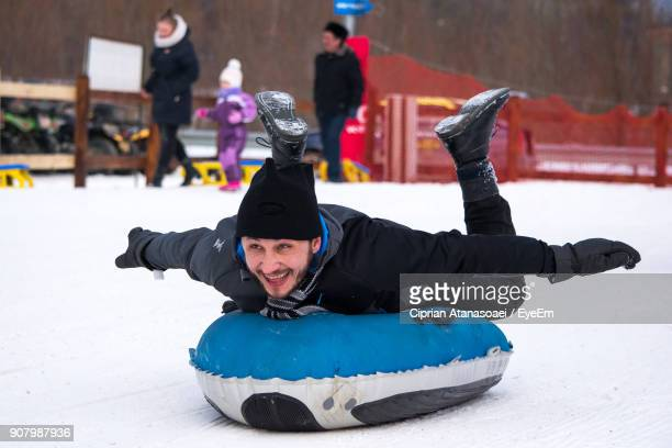 Playful Man Lying On Sled At Snow Field